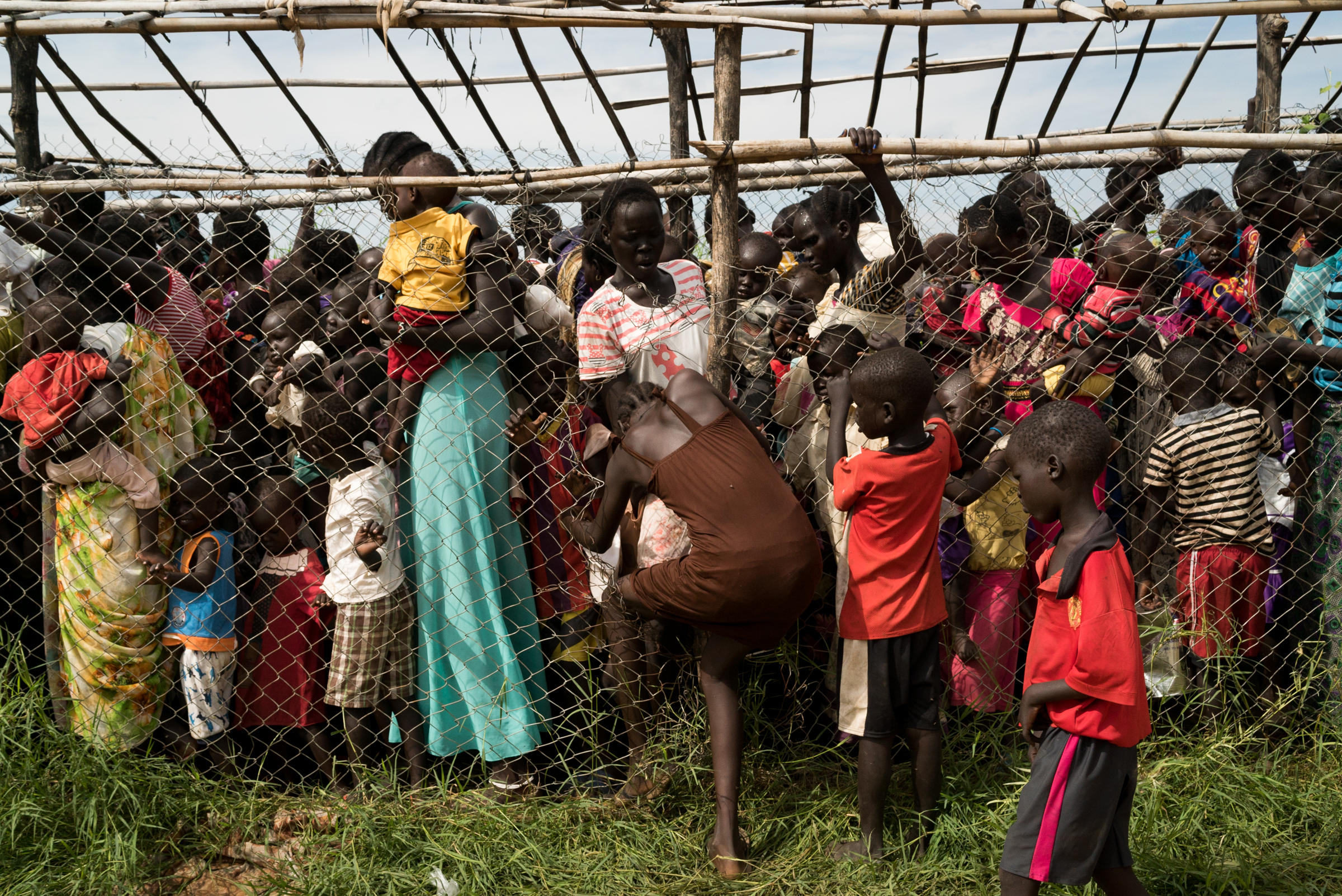 Women and children stand in line while a girl forces her way through the fence in order to receive emergency food at the UN site that houses over 38,000 displaced people i Juba, South Sudan, July 25, 2016.